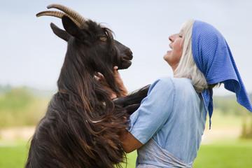 Deutschland, Bayern, Seniorin mit Ziege auf dem Bauernhof
