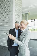 Deutschland, Stuttgart, Geschäftsfrau mit Tablet PC, während Mann am Telefon sprechen