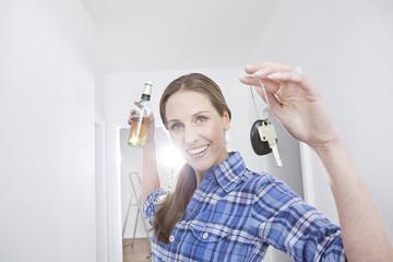 Frau mit Bierflasche und Schlüssel
