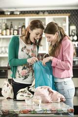 Deutschland, München, Junge Freunde schauen Einkaufstasche in Café an
