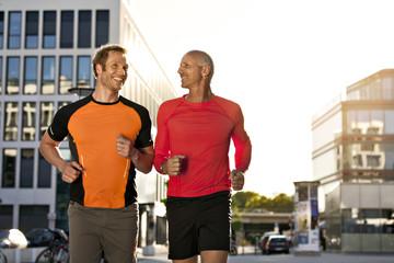 Zwei lächelnde Jogger laufen in der Stadt