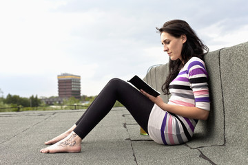 Deutschland, Hamburg, Junge Frau sitzt auf dem Dach und lesen Buch