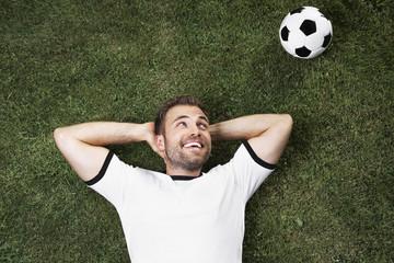 Deutschland, junger Mann liegt auf dem Rasen Blick auf Fußball