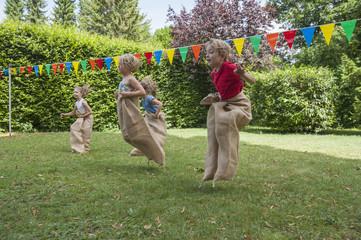 Kinder mit einer Sackhüpfen im Garten auf einer Geburtstagsparty
