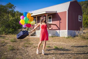 USA, Texas, Junge Frau mit Koffer und Ballon