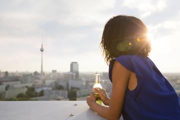 Deutschland, Berlin, junge Frau, Ausschau, halten Bierflasche