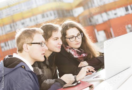 Drei Studenten mit Laptop im Freien