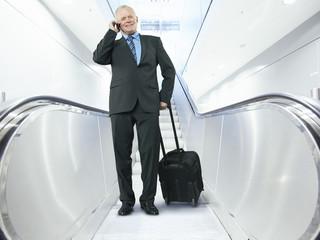 Geschäftsmann sprechen auf Handy mit Aktenkoffer auf Rolltreppe