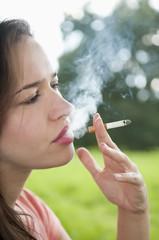 Deutschland, Berlin, junge Frau Raucher Zigarette im Park