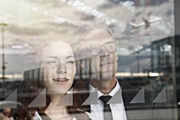 Deutschland, Köln, Junge Frau und älterer Mann schaut durch Fenster am Flughafen