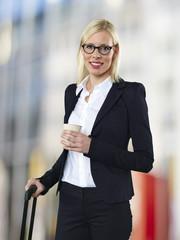 Portrait Geschäftsfrau mit Gepäck und Kaffee zum Mitnehmen