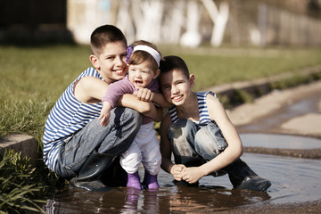 little happy children playing in the puddle