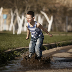 little happy boy jumping in puddle