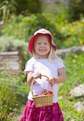 Deutschland, Bayern, Mädchen mit Korb von Erdbeeren im Garten