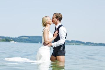 Deutschland, Bayern, Tegernsee, Hochzeitspaar steht im See, küssen