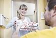Deutschland, Köln, Junge Frau, die Pizza-Kartons aus Lieferung Mann