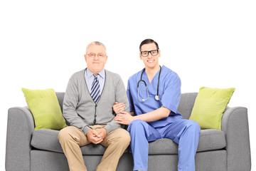 Young doctor and senior gentleman posing on sofa