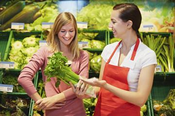 Deutschland, Köln, Junge Frauen mit Sellerie im Supermarkt