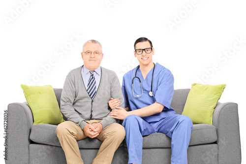 Young doctor and senior gentleman posing on sofa