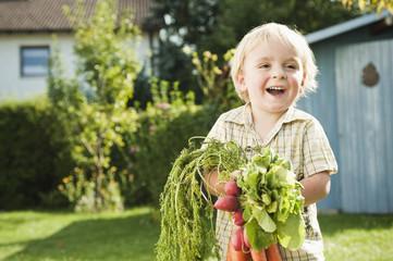 Deutschland, Bayern, Junge hält Radieschen und Karotten