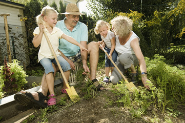 Deutschland, Bayern, Großeltern mit Kindern im Gemüsegarten arbeiten