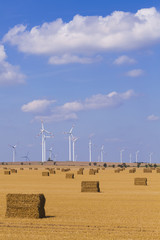 Deutschland, Magdeburg Börde, Stoppelfeld Feld mit Strohballen und Windpark im Hintergrund