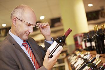 Deutschland, Köln, Mann Inspektion Weinflasche im Supermarkt