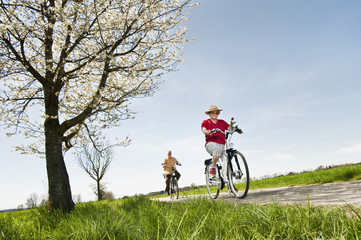 Deutschland, Bayern, Senior Paar fahren Elektro-Fahrrad