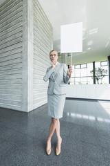 Deutschland, Stuttgart, Geschäftsfrau steht mit leeren Zeichen in Office-Lobby