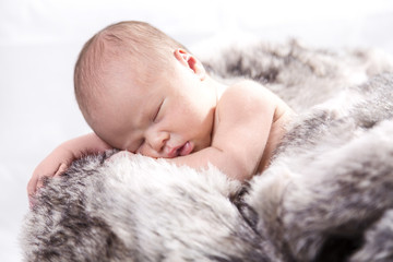 Baby auf Pelz in Holzkorb
