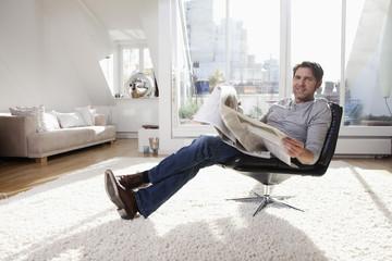 Deutschland, München, Mann liest Zeitung im Wohnzimmer