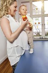 Deutschland, Bonn, Schwangere Mutter essen Apfel mit Sohn im Wohnzimmer