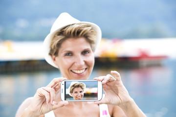 Frau mit Smartphone fotografieren