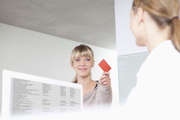 Deutschland, Patient geben Versicherungskarte zu Rezeptionistin in Zahnarztpraxis