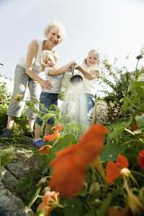 Deutschland, Bayern, Großmutter mit Kindern Blumen gießen