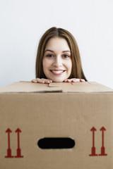 Deutschland, München, Frau stützt sich auf Karton