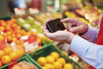 Deutschland, Köln, Mann mit Smartphone im Supermarkt