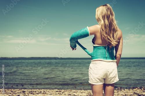 Junge Frau mit verbundenem Arm am Strand