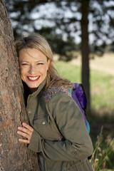 lächelnde Frau an einen Baum gelehnt