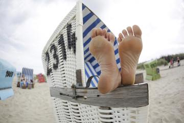 Deutschland, Niedersachsen, Ostfriesland, Langeoog, Füße auf einer Armlehne eines Strandkorb