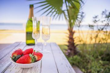 USA, Texas, Schale mit Erdbeeren und Champagner am Strand mit Palme