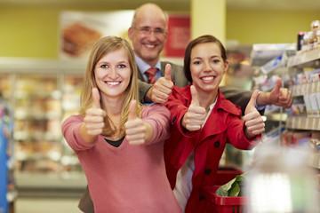 Deutschland, Köln, Mann und Frauen, Daumen hoch im Supermarkt