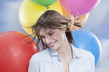 Deutschland, Köln, junge Frau mit Luftballons