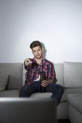 Deutschland, Berlin, Junger Mann sitzt auf der Couch vor der Leinwand