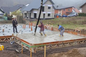Deutschland, Rheinland-Pfalz, Bauarbeiter Füllen Beton für Fundament und Mann mit Fernsteuerung