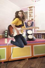 Mädchen springt während Gitarre spielen und Trommeln