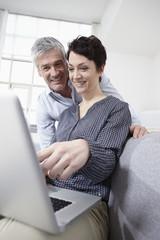 Deutschland, München, Paar mit Laptop zu Hause