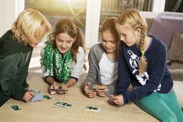 Vier Kinder spielen Kartenspiel im Wohnzimmer