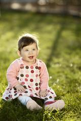 cute sweet baby sitting on grass in garden