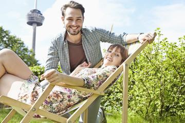 Deutschland, Köln, Junges Paar entspannt im Garten